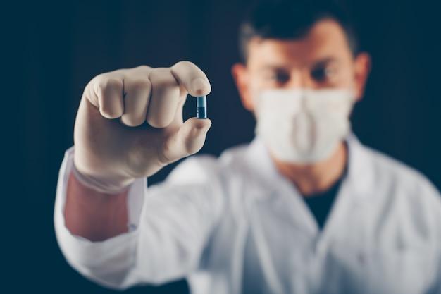 Medico con maschera e guanti tenendo la pillola blu con le dita. vista laterale.