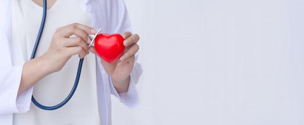 Medico con stetoscopio esaminando il cuore rosso