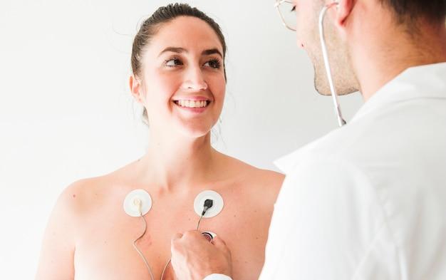 Medico con stetoscopio vicino donna con elettrodi