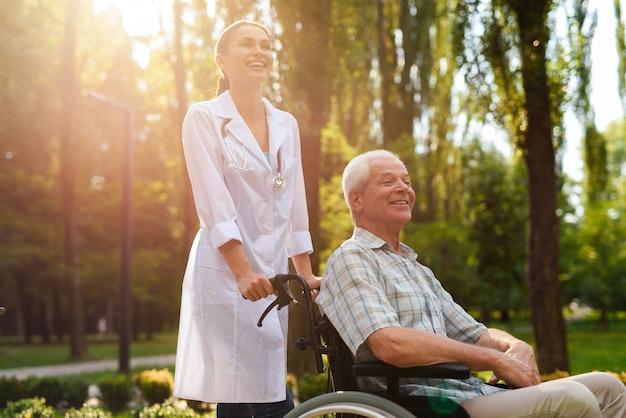 Medico con uomo anziano in sedia a rotelle ridendo