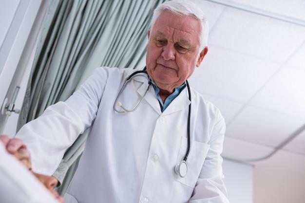 Medico consolante paziente anziano
