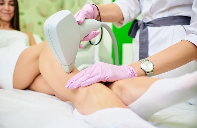 Medico cosmetologo conduce la procedura di depilazione laser dal corpo di una ragazza