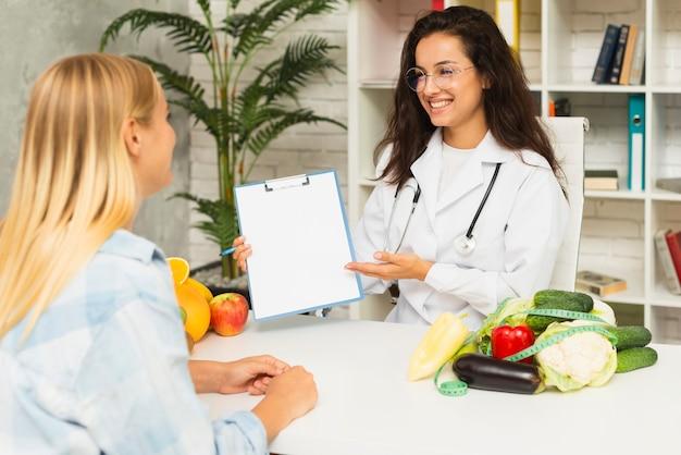 Medico del colpo medio che mostra i risultati al paziente