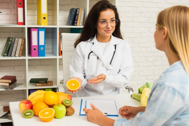 Medico del colpo medio che parla con paziente