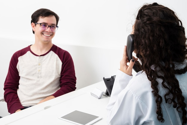Medico del colpo medio che parla sul telefono