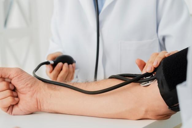 Medico del primo piano che gonfia il polsino di pressione sanguigna