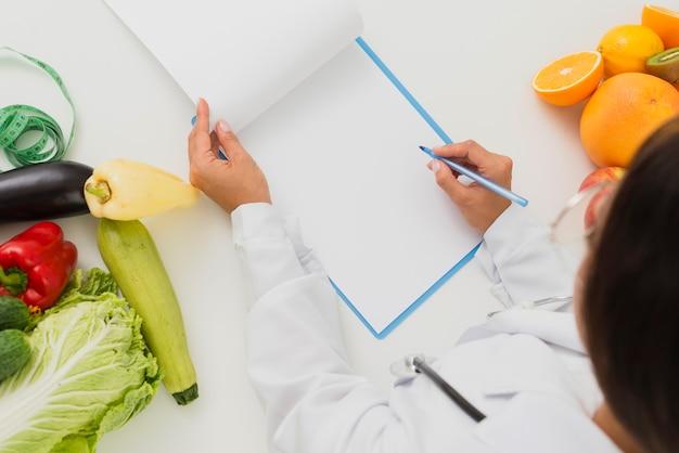 Medico del primo piano con la scrittura di frutta e verdura