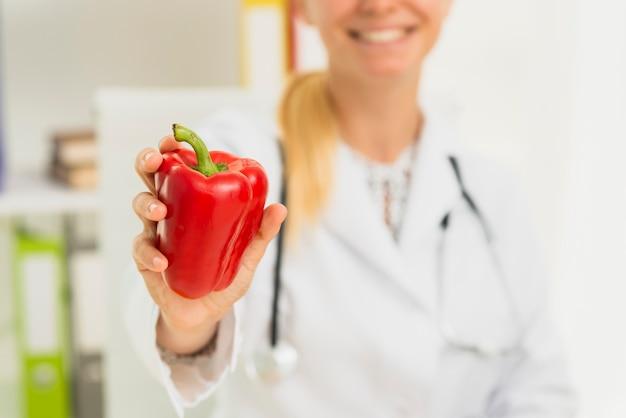 Medico del primo piano con peperone dolce rosso