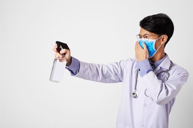 Medico dell'asia che utilizza la pulizia con alcool spray per proteggere l'antivirus