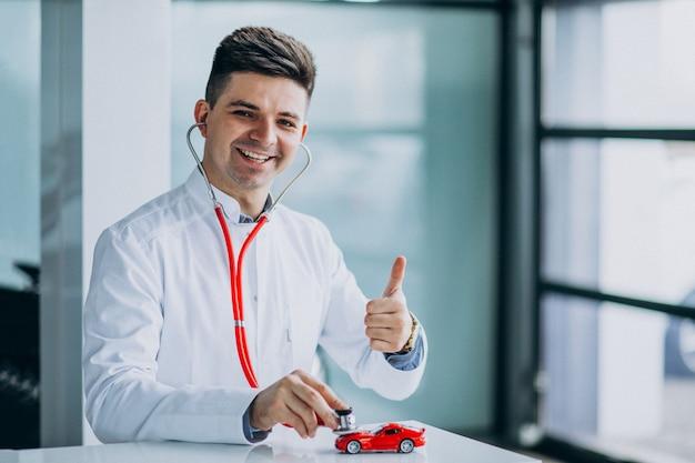 Medico dell'automobile con lo stetoscopio in una sala d'esposizione dell'automobile
