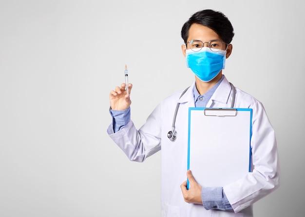 Medico dell'uomo dell'asia che indossa maschera chirurgica e mano che tiene il vaccino s