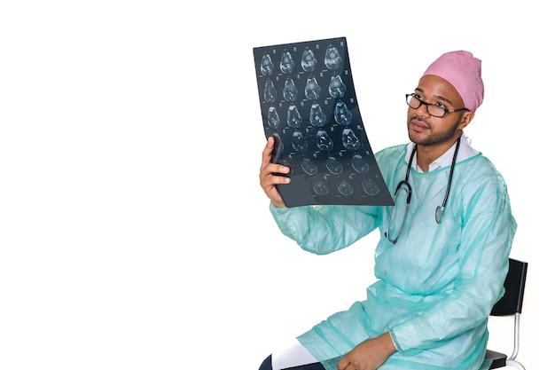 Medico dell'uomo di colore che esamina x ray che indossa un fazzoletto rosa nella lotta contro il cancro, fotografato su un bianco isolato
