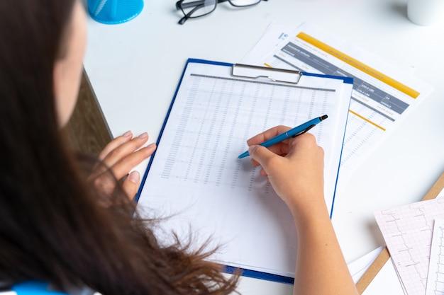 Medico della donna che prende le note sulla lavagna per appunti mentre si siede alla sua tavola in ufficio