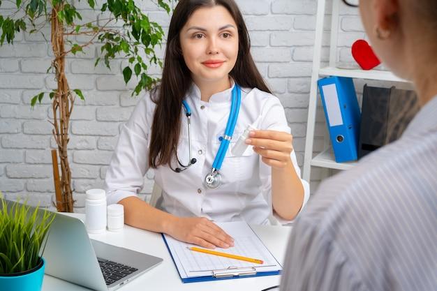 Medico della donna che prescrive una medicina al suo paziente in ospedale