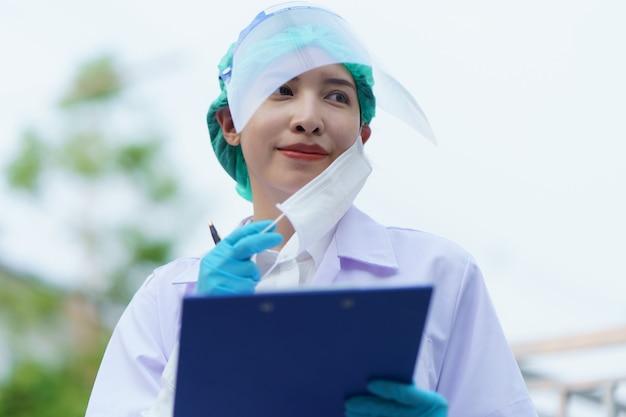 Medico della donna che toglie una maschera per fare una pausa e che tiene il rapporto paziente, ritratto all'aperto, pandemia di coronavirus covid-19.