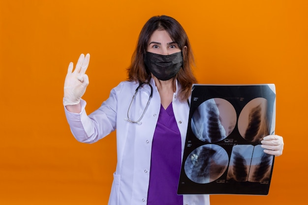 Medico della donna di mezza età che indossa camice bianco nella maschera facciale protettiva nera e con lo stetoscopio che tiene i raggi x dei polmoni che guarda positivo della macchina fotografica che fa segno giusto che sta sopra fondo arancio