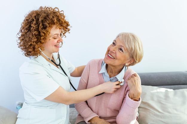 Medico della giovane donna che indossa camice che esamina donna senior