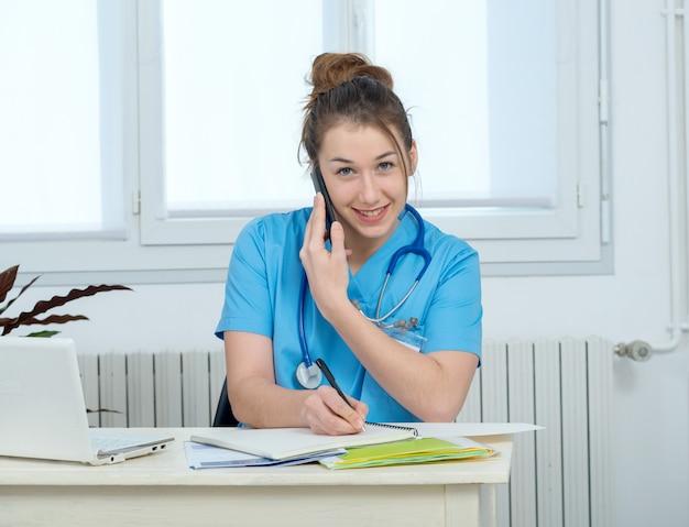 Medico della giovane donna che parla sul telefono
