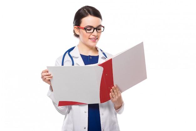 Medico della giovane donna con il raccoglitore della tenuta dello stetoscopio in sue mani in uniforme bianca su bianco