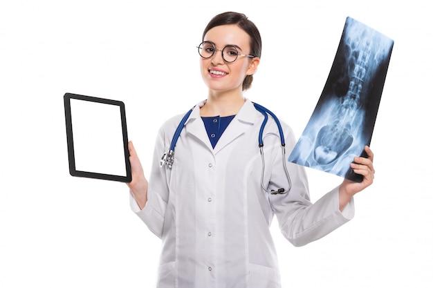 Medico della giovane donna con lo stetoscopio che esamina raggi x che fanno diagnosi in uniforme bianca sul bianco