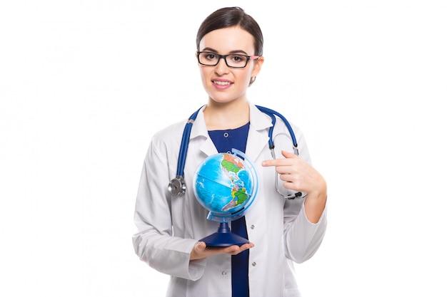Medico della giovane donna con lo stetoscopio che tiene un globo del mondo in sue mani in uniforme bianca su bianco