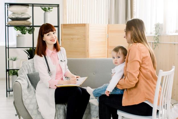 Medico della giovane donna nelle camice che scrive qualcosa in taccuino e madre con la neonata a casa. concetto di medicina, assistenza sanitaria, pediatry e persone