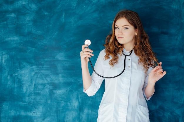 Medico della giovane donna nelle camice e nella mascherina medica. la medicina