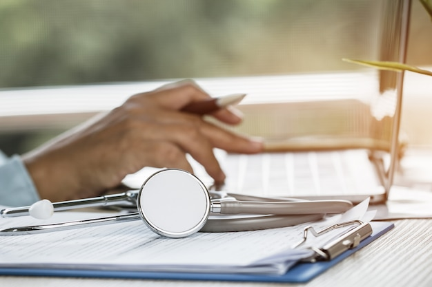 Medico della medicina che utilizza il computer portatile online per il controllo delle informazioni e lo stetoscopio del fuoco all'ospedale