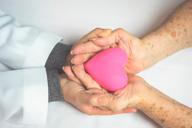 Medico delle giovani donne e mani di eldely che tengono cuore rosa.