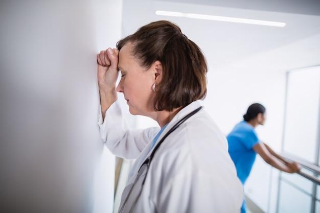 Medico depresso che si appoggia contro la parete