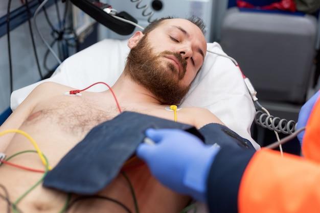 Medico di emergenza che controlla la pressione sanguigna di un paziente nell'ambulanza