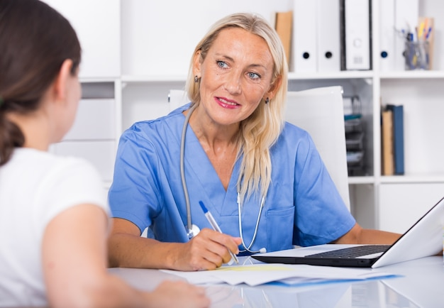 Medico di sesso femminile ascoltando i reclami del paziente