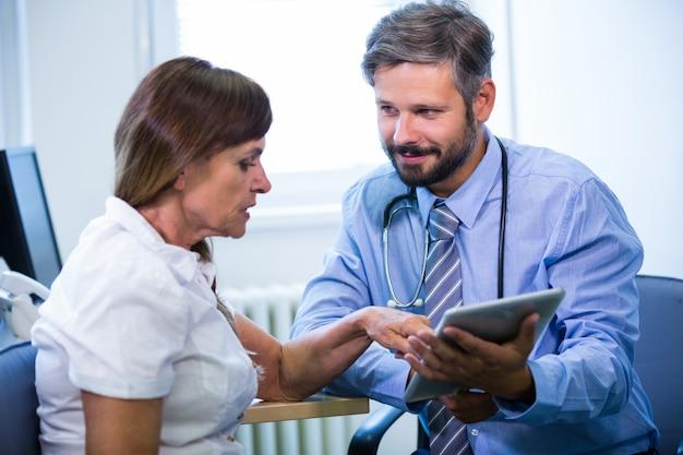 Medico di sesso maschile discutere con il paziente su tavoletta digitale