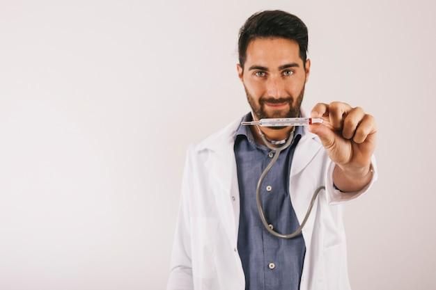Medico di sorriso in posa con il termometro