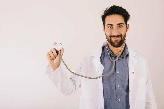 Medico di sorriso in posa con lo stetoscopio