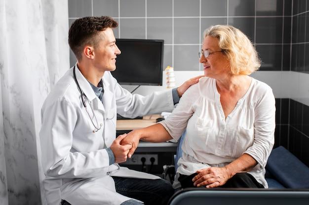 Medico di vista frontale che tiene la mano del paziente