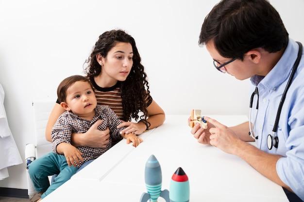 Medico di vista laterale che spiega ad una madre