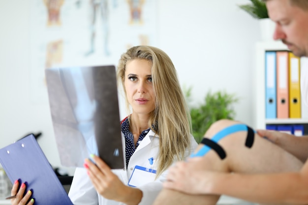 Medico donna con esamina una radiografia della gamba accanto al paziente si siede.
