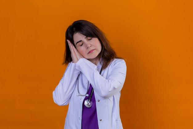 Medico donna di mezza età che indossa camice bianco e con lo stetoscopio alla ricerca oberati di lavoro in posa con le mani insieme mentre in piedi con gli occhi chiusi vuole dormire su sfondo arancione