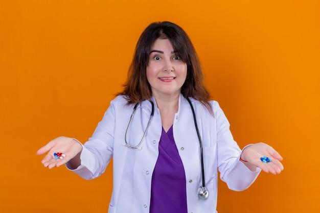 Medico donna di mezza età che indossa camice bianco e con lo stetoscopio tenendo le pillole in mano guardando la fotocamera sorpreso e sorridente in piedi su sfondo arancione