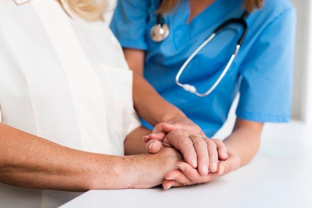 Medico e donna anziana che si tengono per mano primo piano