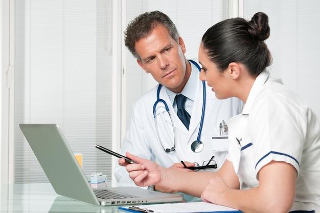 Medico e infermiere che lavora al computer portatile