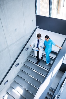 Medico e infermiere discutendo su un rapporto mentre scendendo le scale