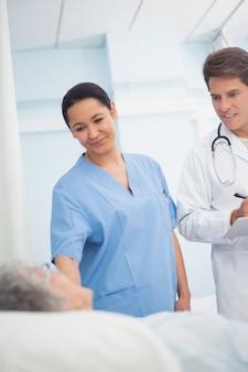 Medico e infermiere guardando un paziente