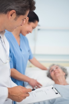 Medico e infermiere in piedi accanto a un paziente