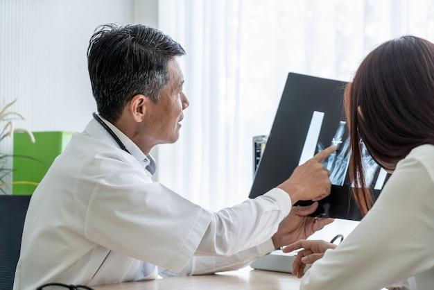 Medico e paziente asiatici stanno discutendo