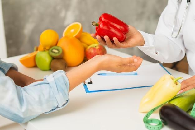 Medico e paziente del primo piano con peperone dolce rosso