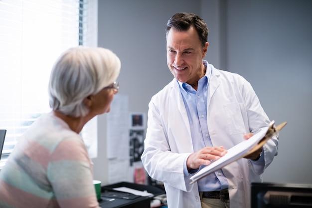 Medico e paziente senior che discutono sulla lavagna per appunti