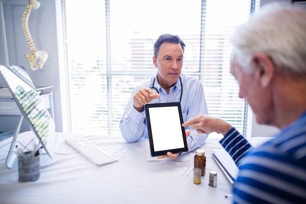 Medico e paziente senior che per mezzo della compressa digitale