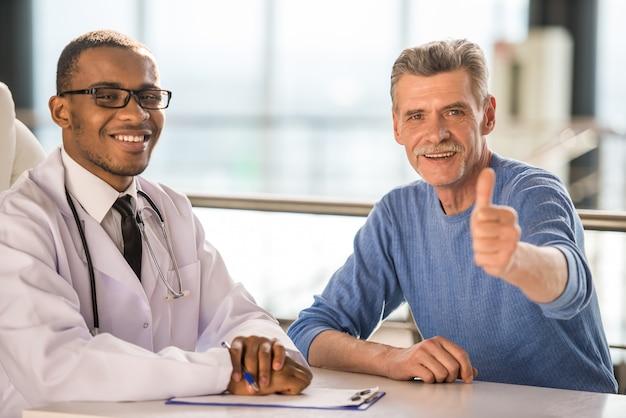 Medico e paziente sorridente e pollice in alto.